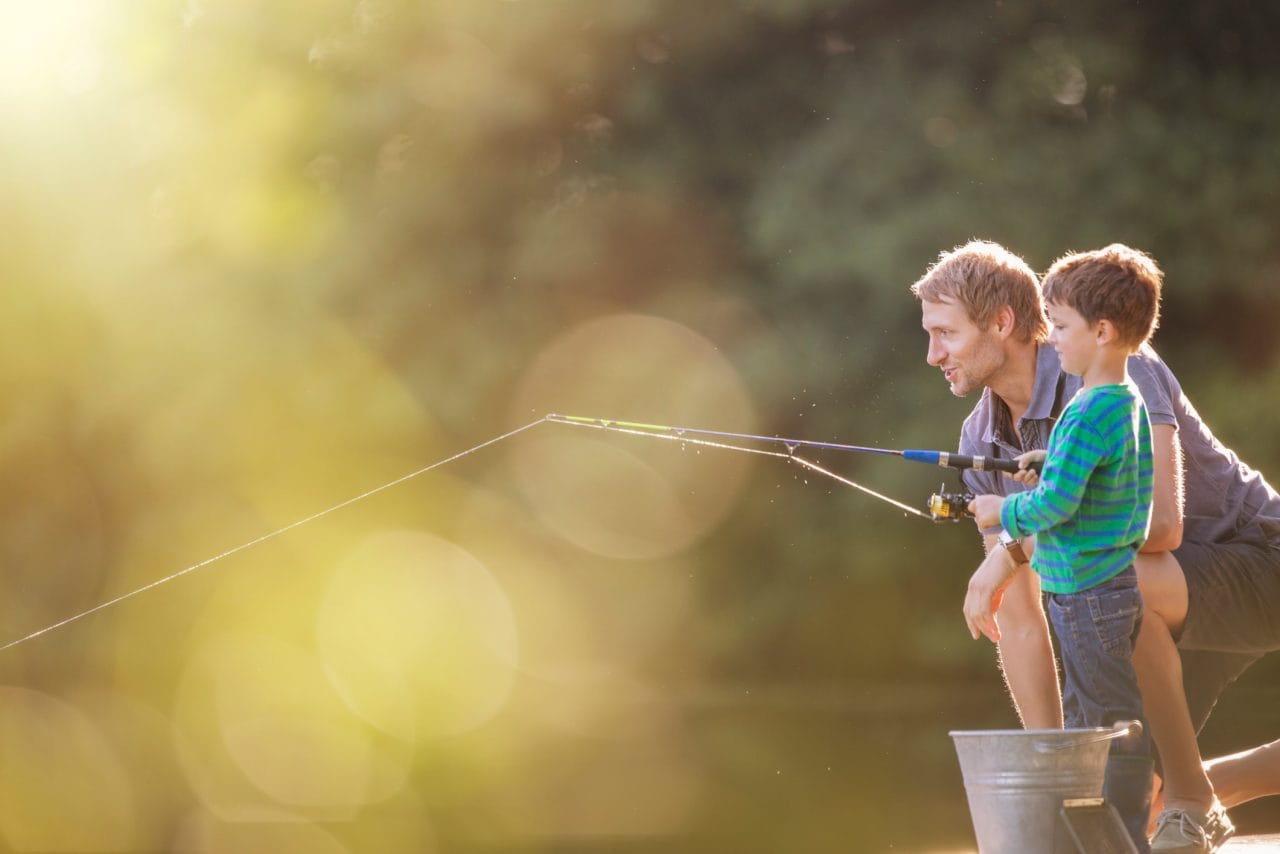 Father and son fishing in lake